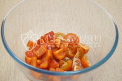 В миску нарезать кусочками нарезанный перец и четвертинками нарезанные помидоры.