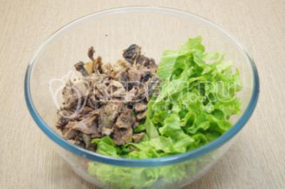 Добавить нарезанные листики салата и консервированный тунец.