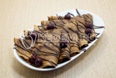На тарелки выложить блинчики и полить растопленным шоколадом и украсить ягодами.