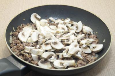 Добавить нарезанные грибы в сковороду и готовить еще 2-3 минуты. Посолить и поперчить по вкусу.