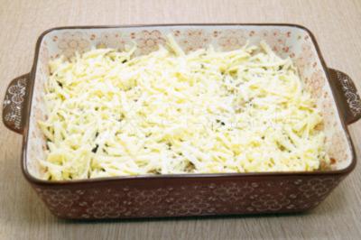 Посыпать половиной тертого сыра.
