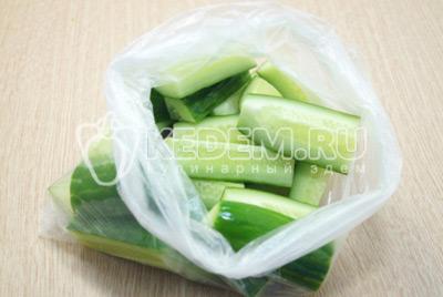 В чистый пакет уложить нарезанные продолговатыми дольками огурцы.
