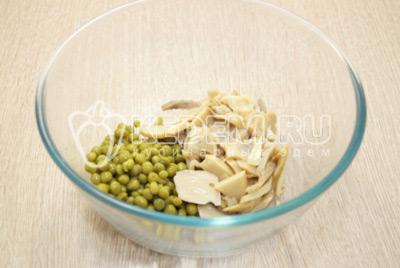 В миске смешать маринованные шампиньоны и зеленый горошек.