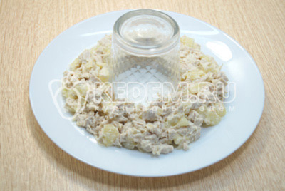 На блюдо установить стакан и выложить слой курицы с ананасами.