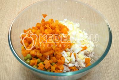 Добавить в миску кубиками нарезанные яйца и морковь.