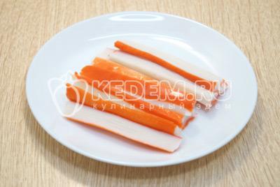 Крабовые палочки нарезать вдоль на половинки, далее нарезать соломкой.