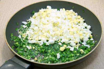 Добавить нашинкованные яйца, перемешать и посолить начинку.