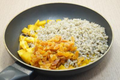 В сковороду с тыквой добавить отварную перловку и нарезанную курагу.