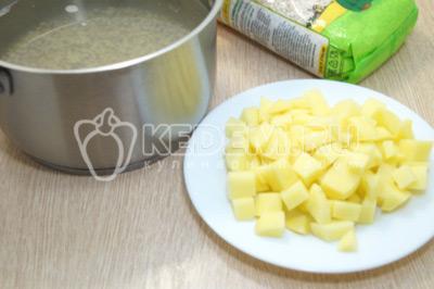 Добавить к крупе кубиками нарезанный картофель и варить еще 5-7 минут.