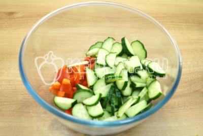 В миску нарезать кусочками болгарский перец и ломтиками огурцы.