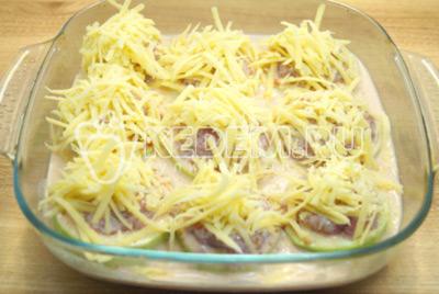 Добавить тертый сыр сверху кабачков.