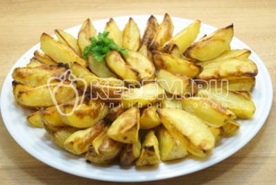 Картофельные дольки выложить на блюдо.