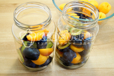 Разделить абрикосы и сливы на половинки, удалить косточки и сложить в банки.