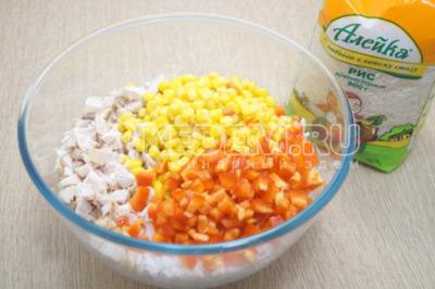 В миске смешать отваренный рис, кубиками нарезанное копченое куриное филе, консервированную кукурузу и кубиками нарезанный болгарский перец.