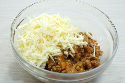 Немного остудить начинку и выложить в миску, добавить 100 г тертого сыра. Перемешать.