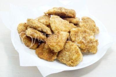 Готовые наггетсы выложить на блюдо с бумажным полотенцами, удалив лишнее масло.